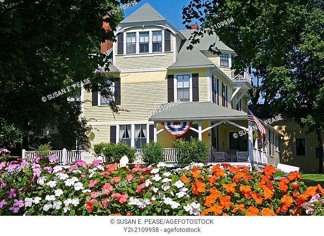Flowers frame a view towards a large yellow house, Bar Harbor, Maine, United States