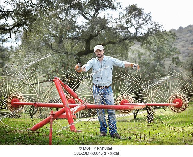 Man on farm with hay rake