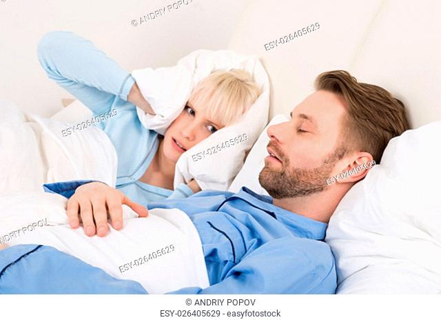 Young Woman Covering Her Ears With Pillow While Man Snoring At Home