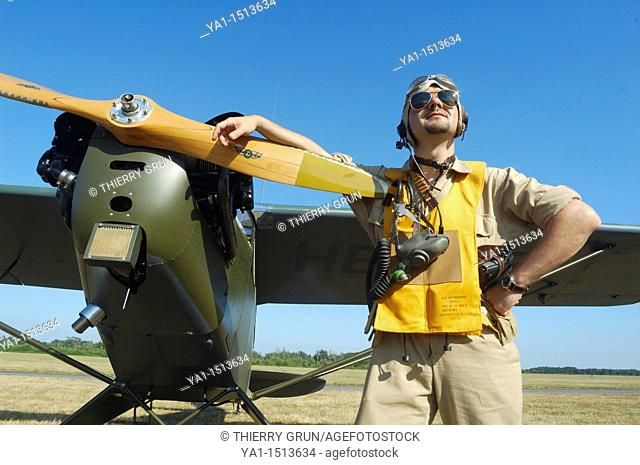 Pilot in WWII US Army uniform front of a Piper J-3 Cub (also ref L-4)