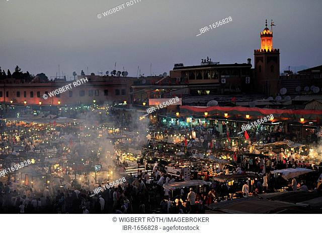 Evening at the Djemaa el Fna market square, literally meaning Assembly of the Dead, with smoke from the many food stalls, behind, the minaret of a mosque
