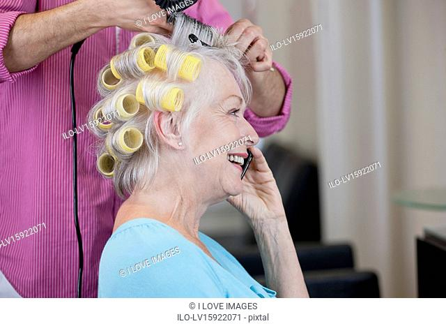 A senior woman talking on a mobile phone whilst having her hair dried