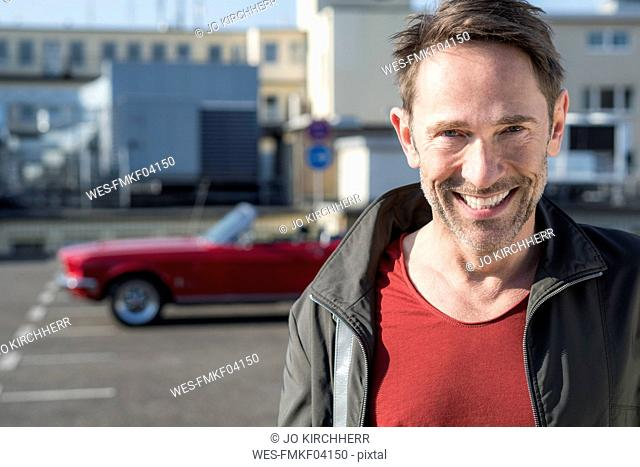 Portrait of smiling mature man in front of his sports car on parking level