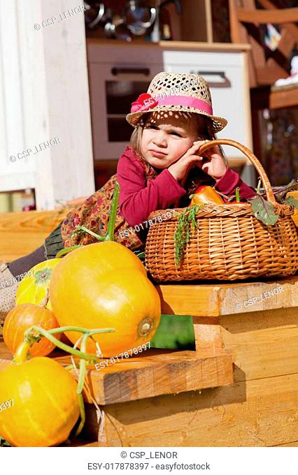 child in a straw hat sits on wooden steps with pumpkins