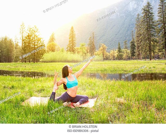 Woman practicing yoga pose by lake in Yosemite National Park, California, USA
