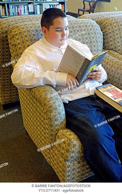 Preteen Boy Reading a Book in Book Store, Rochester, New York, USA