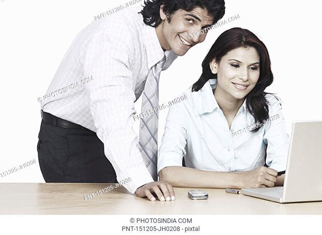 Portrait of a businessman and a businesswoman using a laptop