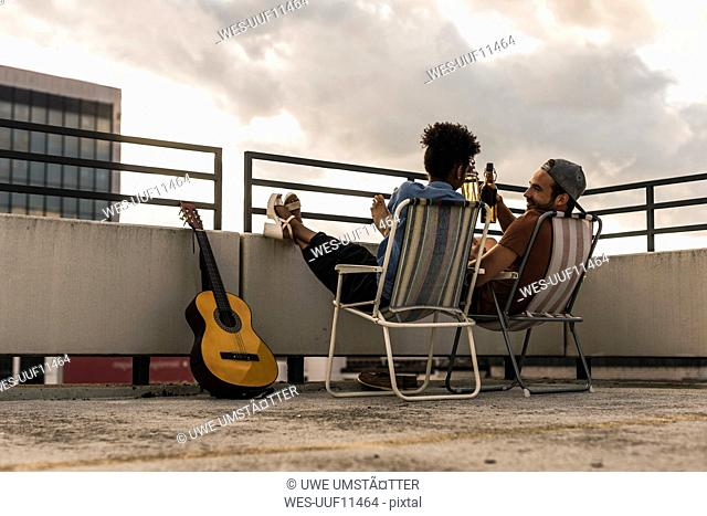 Young couple with beer and guitar sitting on rooftop