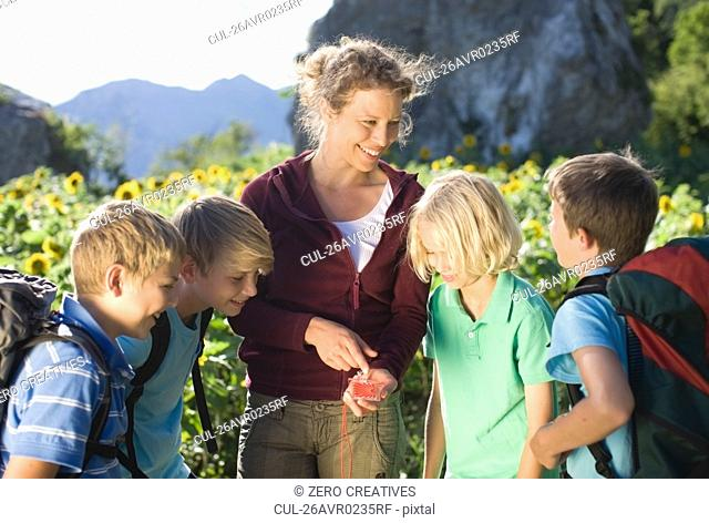 Woman explaining a compass to boys