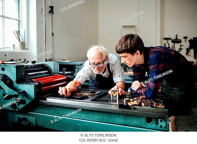 Senior craftsman teaching young craftsman to use letterpress machine in book arts workshop