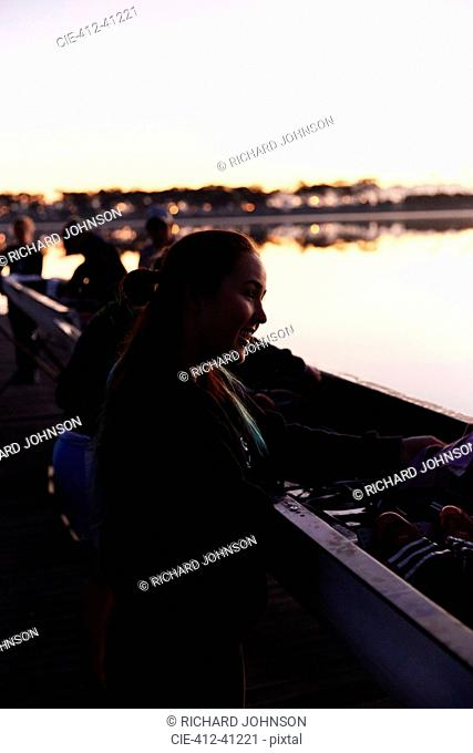 Smiling female rower at scull at sunrise lake
