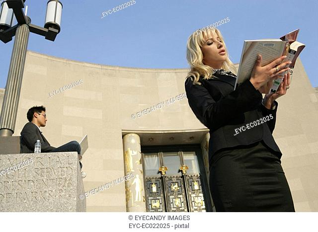 woman reading a book standing outside