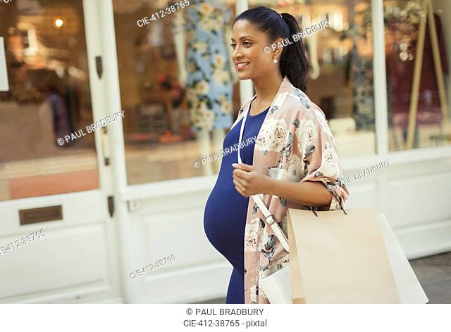 Smiling pregnant woman with shopping bags walking along storefront