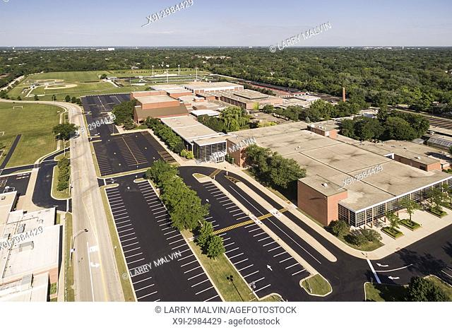 Aerial view of a high school with parking lot and ballfields in a suburban setting in Northbrook, IL. USA