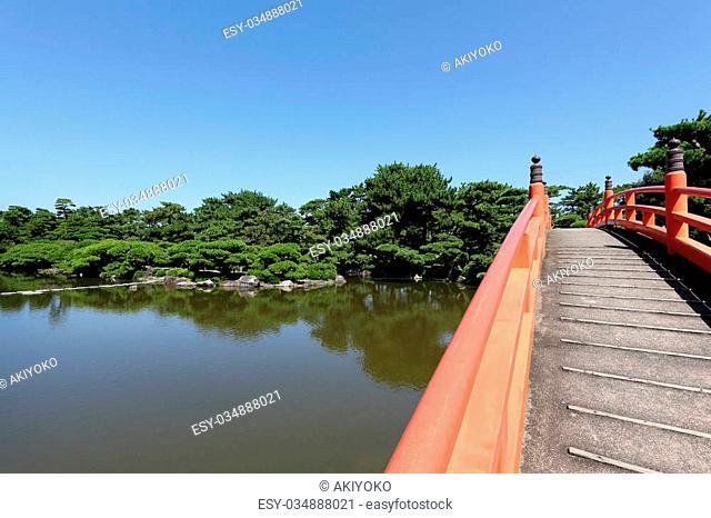 Japanese garden with red wooden bridge