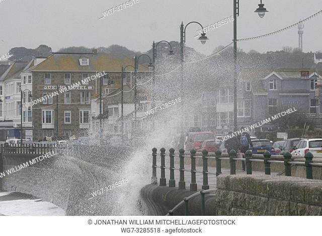 PENZANCE, CORNWALL, UK - 14 April, 2019 - Pedestrians brave the guanlet of large waves crashing against the seafront at Penzance Cornwall UK today as high winds...
