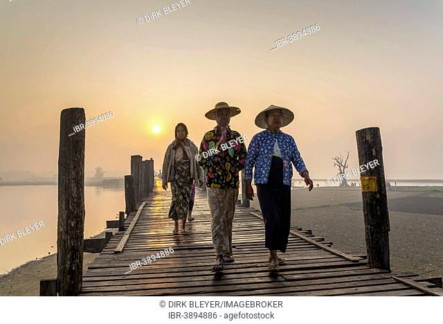 Women wearing traditional hats on a teak bridge, U Bein Bridge over Taungthaman Lake at sunrise, Amarapura, Mandalay Division, Myanmar