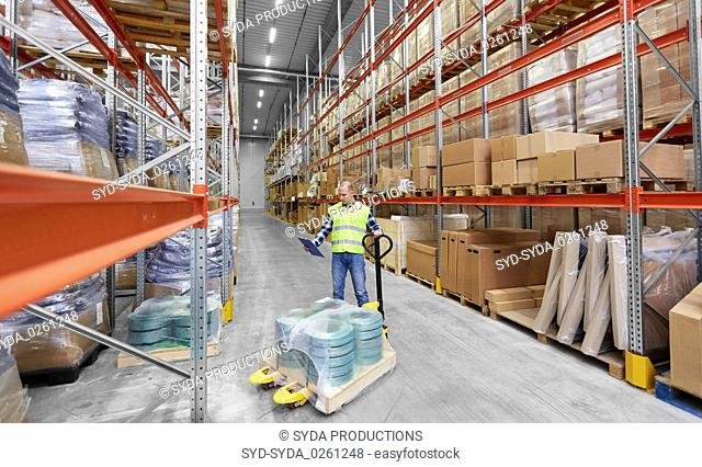 male worker with loader and clipboard at warehouse