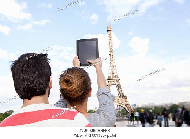 France, Paris, couple photographing Eiffel Tower with tablet computer, back view