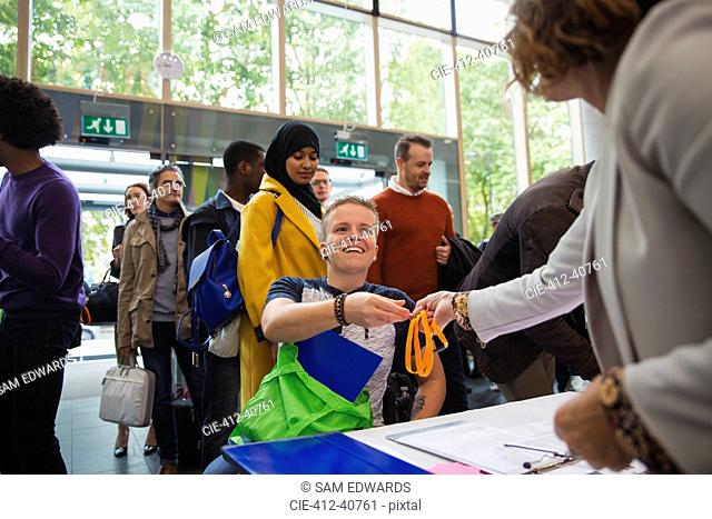 Smiling woman in wheelchair arriving and checking in at conference registration table