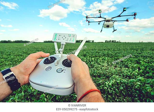 The man control octocopter or remote control for the drone in the hands for take a picture on sky. Agriculture drone flies over the green field