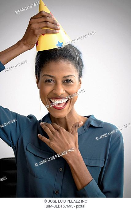 Mixed race businesswoman wearing party hat