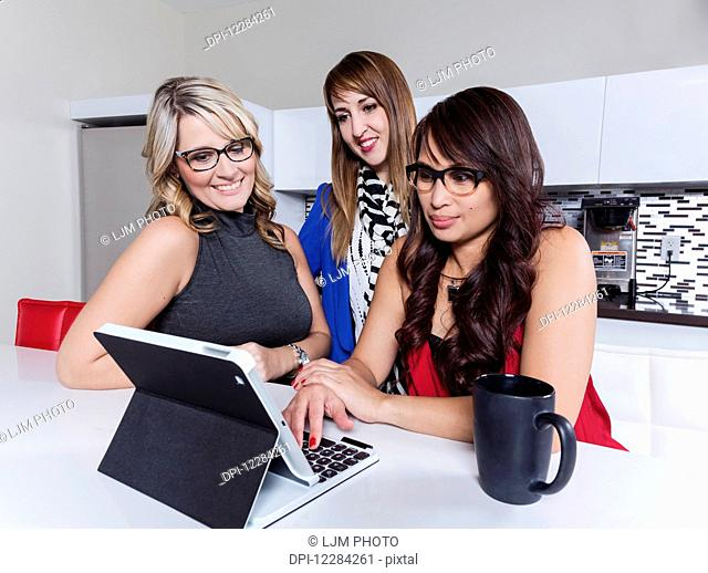 Three professional business women looking on social media while taking a break in an office kitchen area; St. Albert, Alberta, Canada