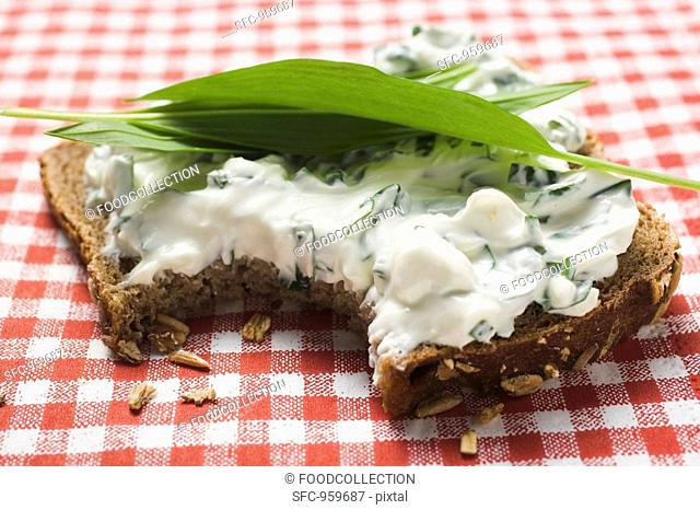 Quark and ramsons on wholemeal bread, a bite taken