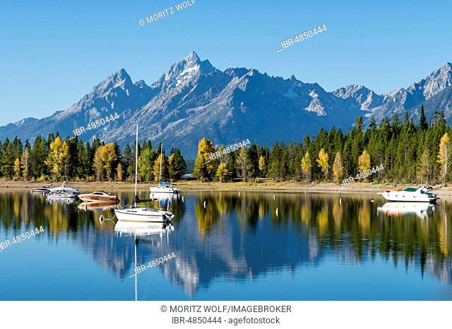 Mountains reflected in the lake, Jackson Lake, sailing boats in a bay, Colter Bay, Teton Range mountain range, Grand Teton National Park, Wyoming, USA