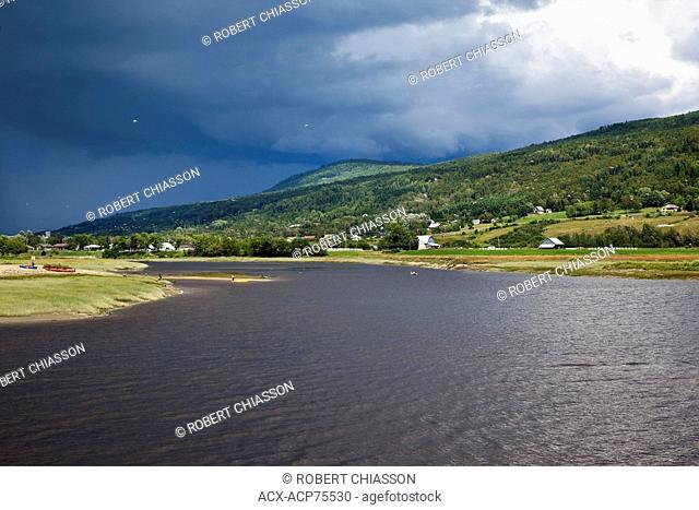 Dark clouds advancing over Riviere du Gouffre (Gouffre River) at the point where it empties into the St. Lawrence River. The area is the point of departure and...
