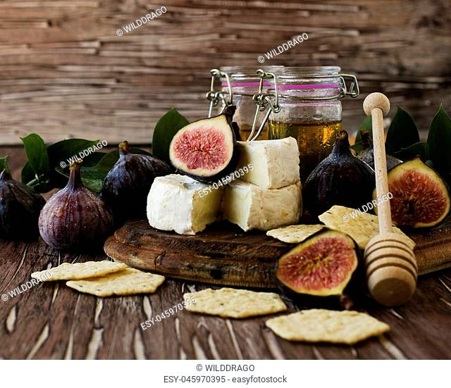 figs with cheese and honey on a wooden table selective focus