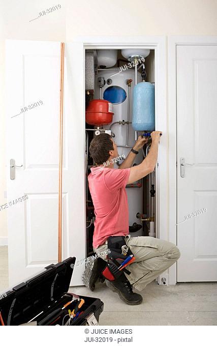 Handyman fixing boiler in closet