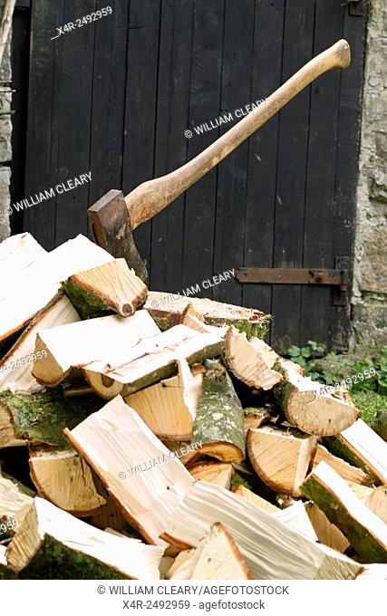 A pile of split logs, which will be used for firewood, with the axe used for splitting the wood buried in a chopping block