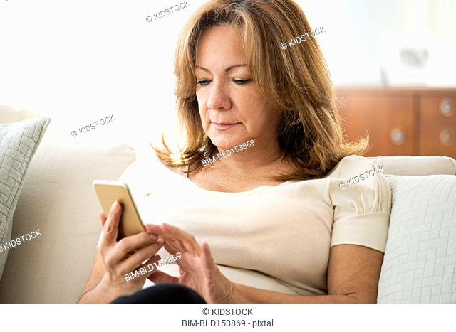 Older Hispanic woman using cell phone on sofa