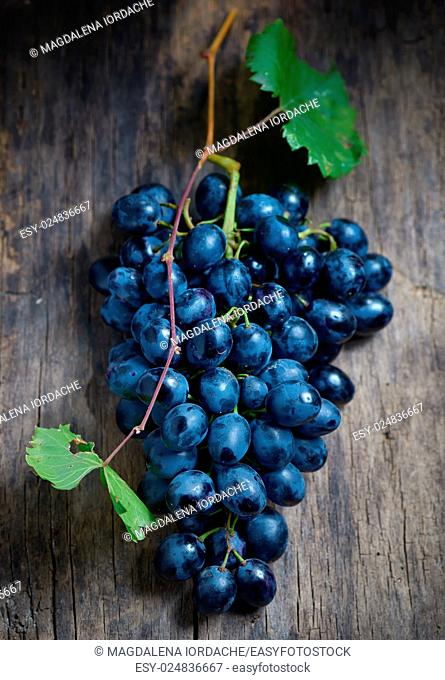 Bunch of red grapes on wooden table background