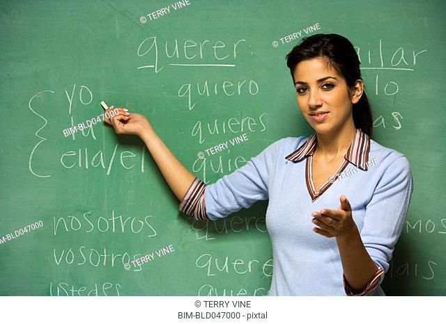 Hispanic female teacher in front of blackboard