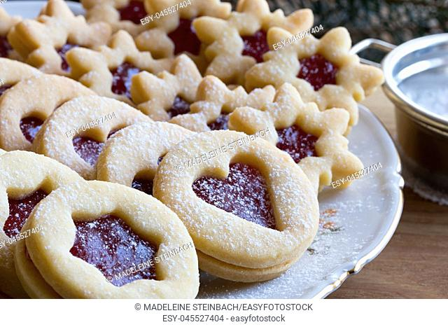 Linzer Christmas cookies filled with strawberry jam and dusted with sugar, arranged on a plate on a table