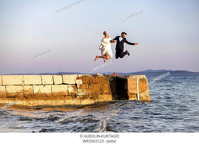 Bride and groom on pier jumping into the air