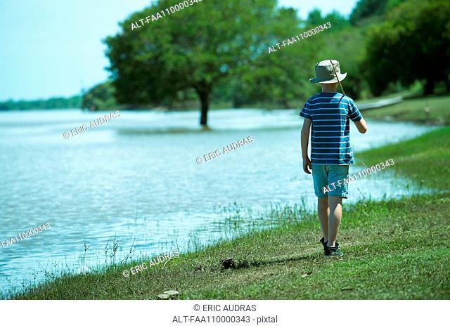 Boy walking along lake shore with fishing rod, rear view