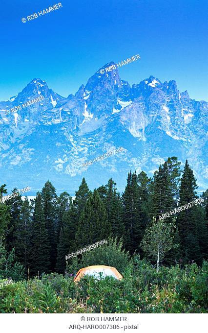 A Tent In A Meadow In Front Of The Grand Teton Mountains, Jackson Hole, Wyoming