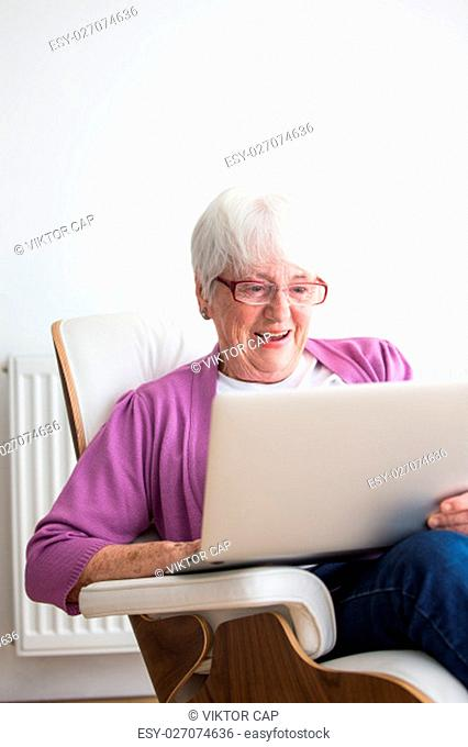 Portrait of a senior woman at home - Laughing at something on her laptop computer, sitting in her favorite chair, enjoying retirement