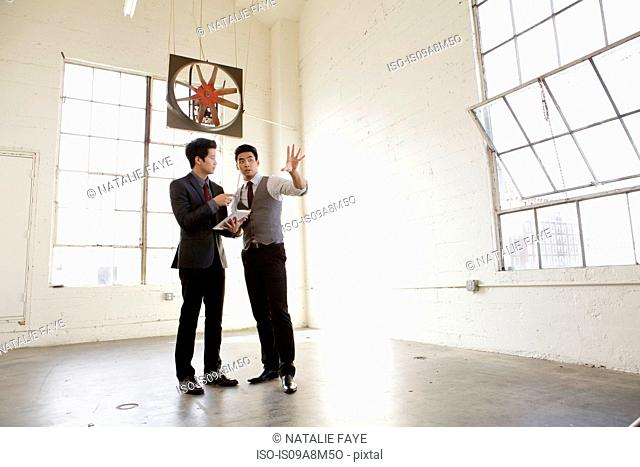 Two young men holding discussion in empty office