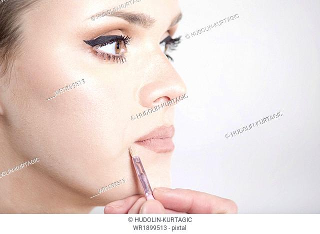 Young woman applying make-up on her face