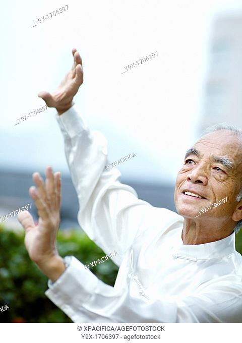 William Ng, a Tai Chi master practicing Tai Chi on the deck of The Peninsula Hotel, overlooking Hong Kong Victoria Harbour skyline