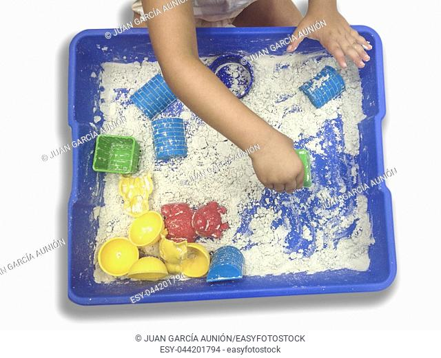 Little girl playing with magic motion sand. Tools and moulds ready to use
