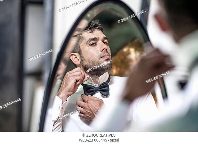 Man looking in mirror adjusting collar