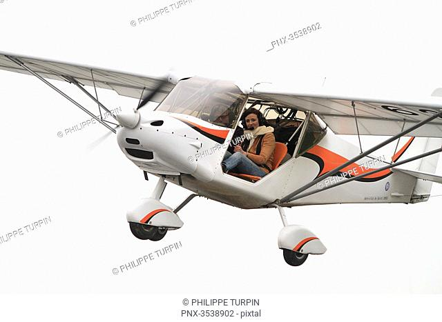 Pilot young woman taking off on board of a microlight