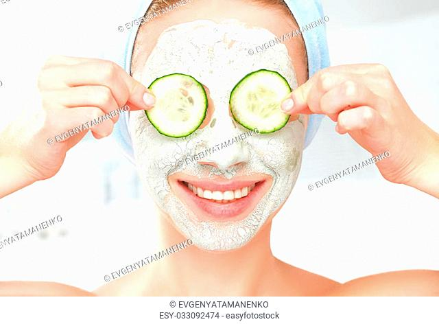 Funny young girl with a mask for skin face and cucumbers on eyes