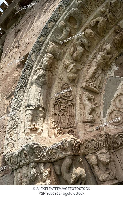 Man with chains binding his neck and feet. Detail of portal of Romanesque church San Andrés (12th century) in Soto de Bureba, province Burgos, Castile and Leon