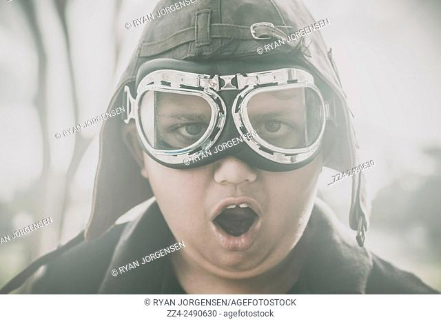 Retro photograph of a young surprised kid wearing retro pilot cap and glasses in cold misty fog. Travel adventure in imagination